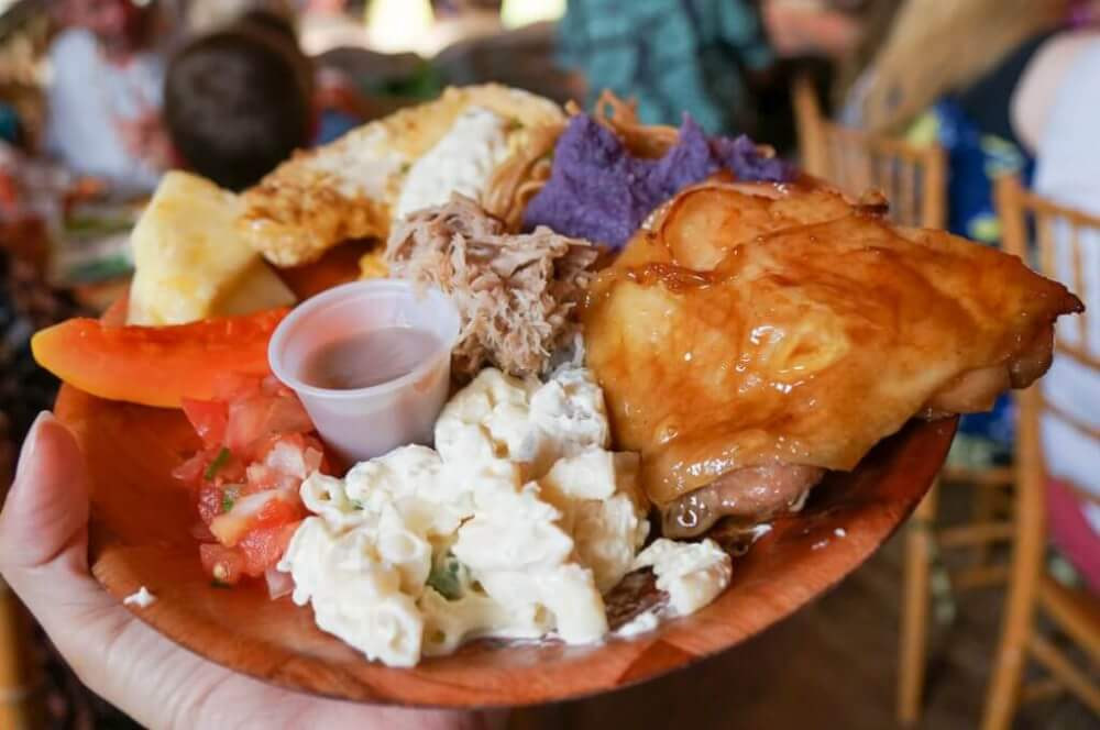 Luau Kalamaku has some of the best luau food on Kauai! Image of a plate with chicken, kalua pork, lomi lomi salmon, macaroni salad, and more!
