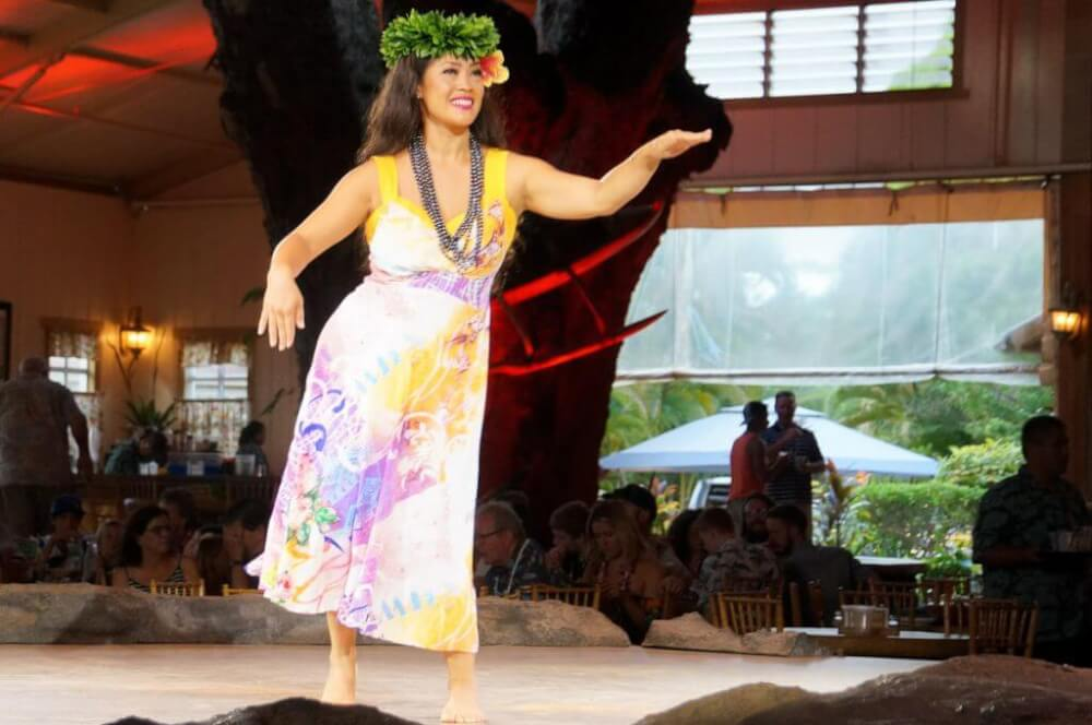 This Kauai luau offers hula dancing during dinner and then an after dinner theatrical show. Image of a woman hula dancing on stage.