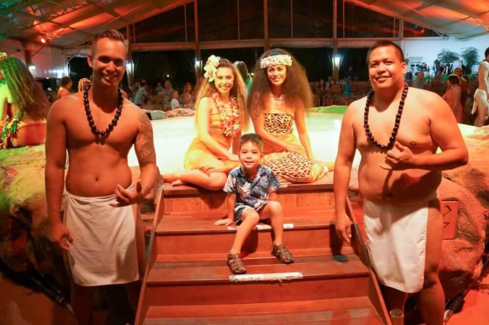 Luau Kalamaku is a kid friendly Kauai luau. Image of a boy posing with a bunch of hula dancers.