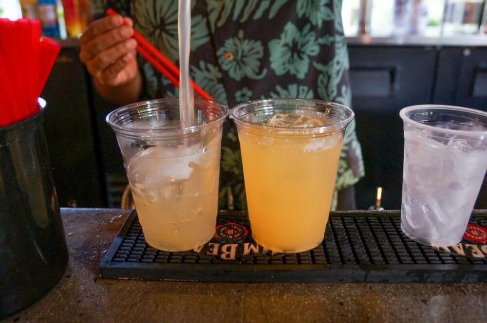 Photo of someone in an Aloha shirt pouring drinks at a Kauai luau.