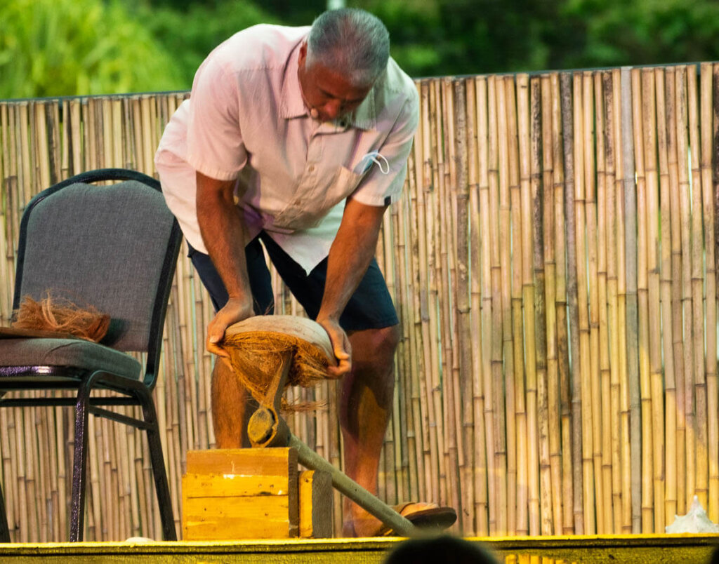 Learn how to husk a coconut at the Ahi Lele Fire Show on Kauai. Image of a man using a tool to break open a coconut on stage.