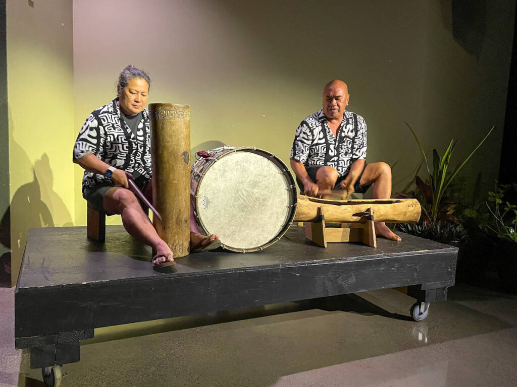 One of the Polynesian drummers at the Ahi Lele Fire Show on Kauai was from the famous Hawaiian band Hapa! Image of two musicians playing Polynesian drums.