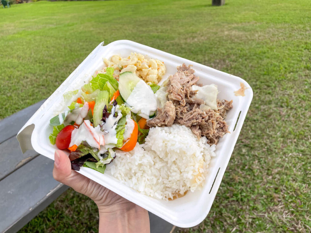 You'll get tasty Kauai luau food at this Hawaiian fire dancer show in North Shore Kauai. Image of a takeout container with kalua pork, macaroni salad, green salad, and rice.