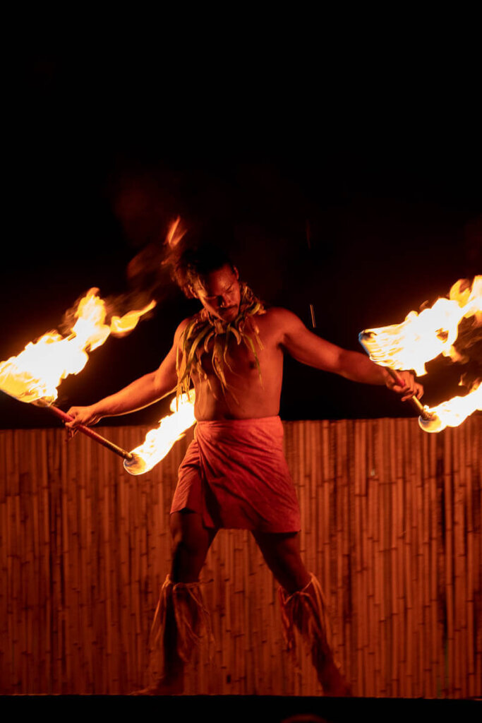 Check out the Ahi Lele Fire Show if you want to see Hawaiian fire dances. Image of a man with 2 fire torches.