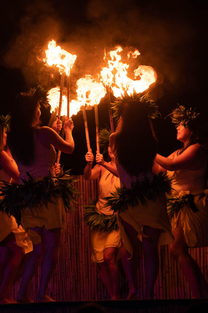 See Tahitian fire dancing at the Ahi Lele Fire Show on Kauai. Image of Tahitian dancers holding torches while dancing in a circle.