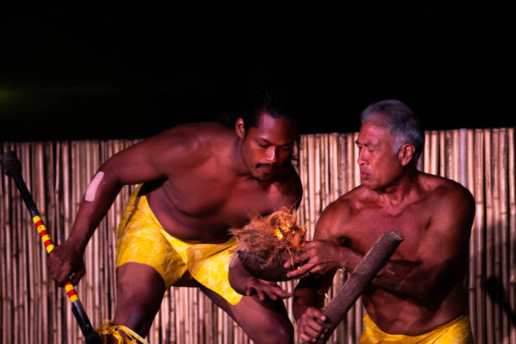 Learn how to make a fire using coconut husks on Kauai. Image of two men marveling at coconut husks on fire.