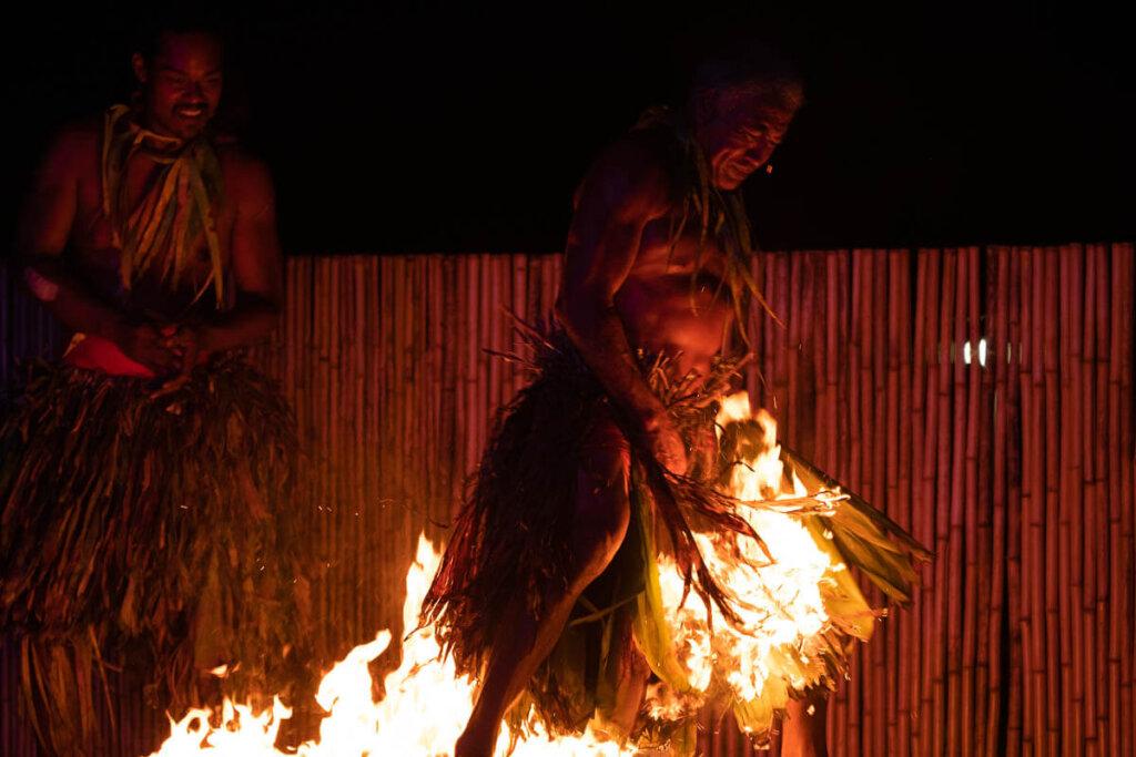 See dancers walk across fire at this Hawaiian fire dancer show. Image of a man wearing a grass skirt walking across fire.