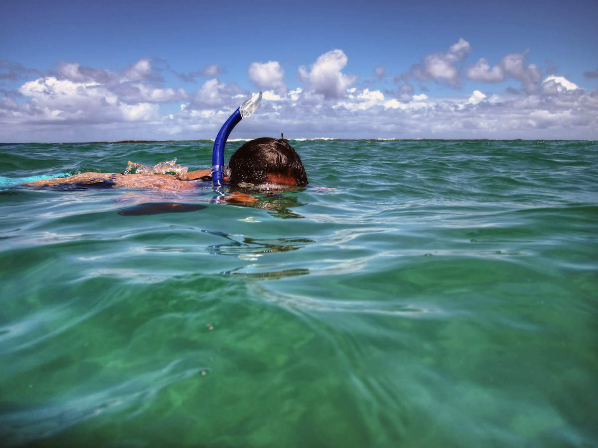 Find out the best Kauai snorkel tours recommended by top Hawaii blog Hawaii Travel with Kids. Image of a man snorkeling at Tunnels Beach on Kauai