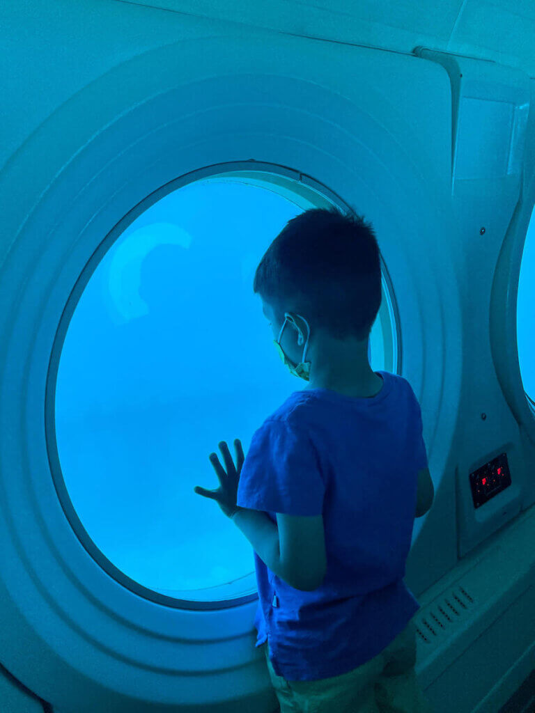 The Waikiki submarine is one of the best kid friendly things to do in Waikiki. Image of a boy in a submarine.