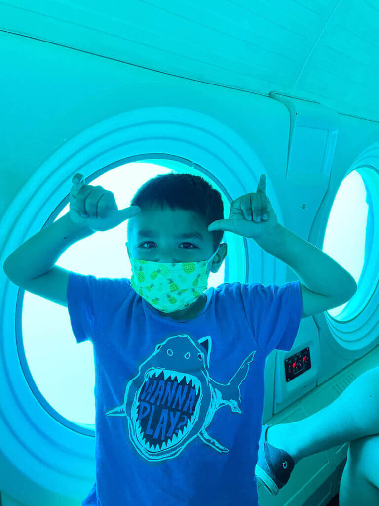 Is this Oahu submarine tour worth it? My kids say YES! Image of a boy wearing a shark shirt throwing 2 shakas in a Waikiki submarine.