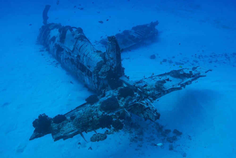 Want to explore Hawaii off the beaten path? Check out the Corsair Plane Wreck dive site, one of the best hidden gems in Hawaii. Image of a sunken plane.