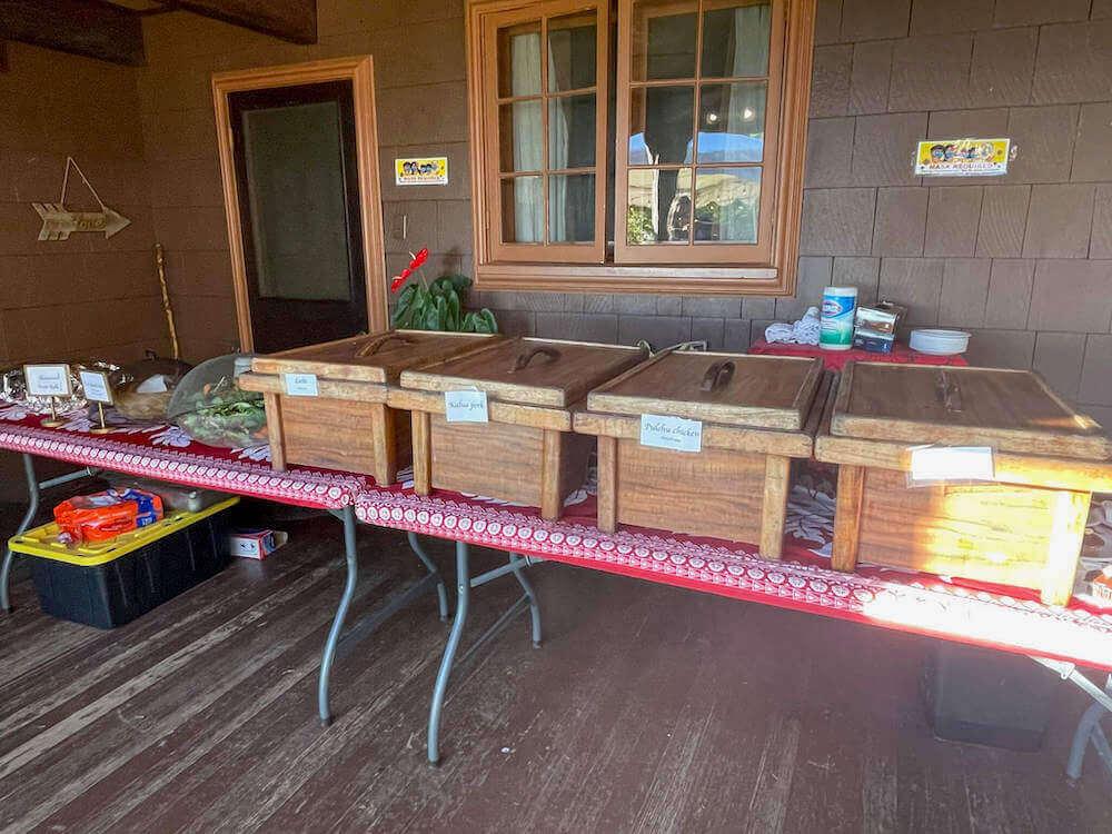 Nutridge Luau has incredible Hawaiian food. Image of Hawaiian food in wooden boxes on a table.