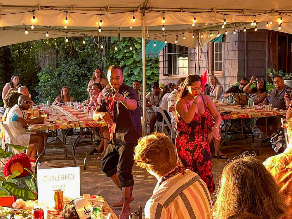 Image of a male and female hula dancer performing in an outdoor tent.