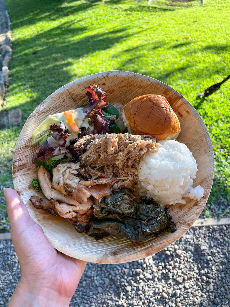 Try traditional Hawaiian food at Nutridge Luau on Oahu. Image of a plate with chicken, kalua pork, rice, salad, and more.