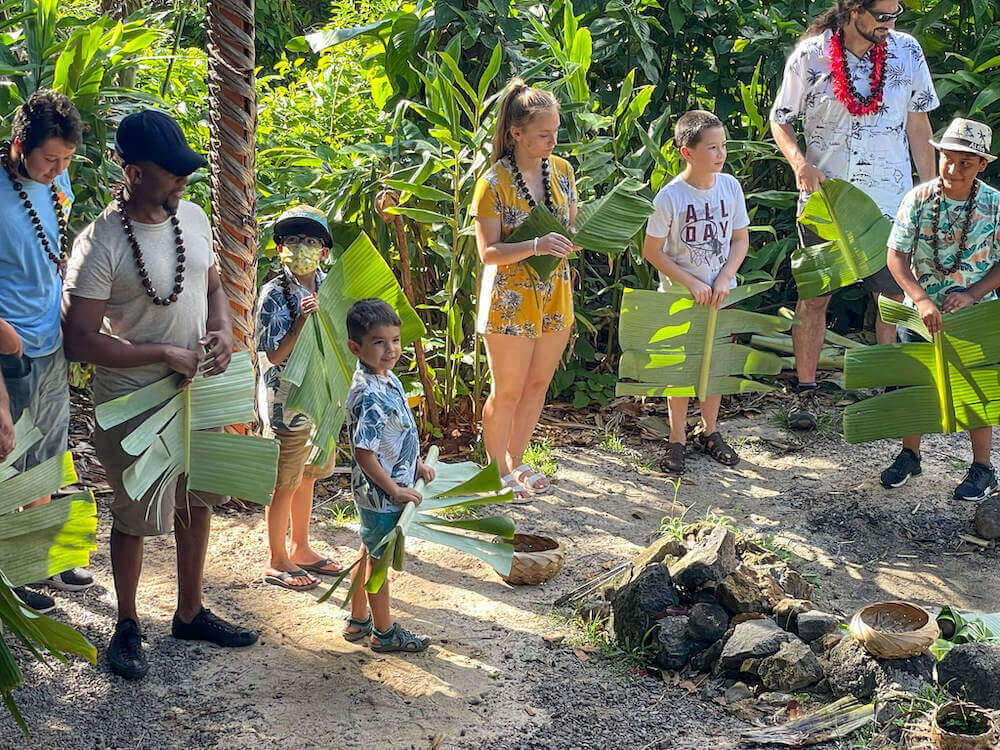 Kids get to participate in activites at Experience Nutridge Luau on Oahu. Image of people holding leaves by an imu on OAhu.
