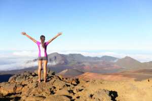 Find out the best Haleakala tours on Maui recommended by top Hawaii blog Hawaii Travel with Kids. Image of a woman standing on the summit of Haleakala Crater at Haleakala National Park.