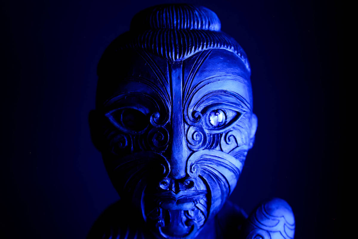 Find out the most haunted places in Hawaii worth checking out by top Hawaii blog Hawaii Travel with Kids. Image of a Polynesian mask with creepy blue lighting on it.