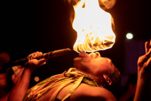 Want to see some amazing Hawaiian fire dancers? Read this detailed Ahi Lele Fire Show review of this new Kauai luau by top Hawaii blog Hawaii Travel with Kids. Image of a man eating fire on Kauai.