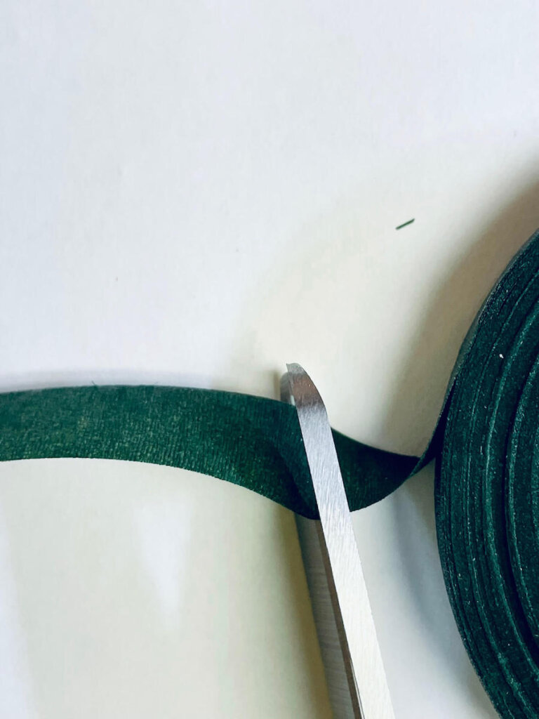 Image of scissors cutting a piece of green floral tape.