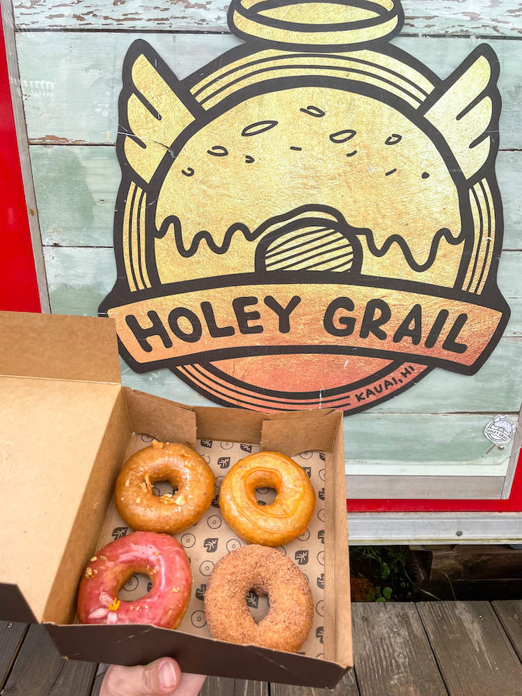 One of the best places to eat in Hanalei for breakfast is Holey Grail food truck. Image of a box of 4 donuts in front of the Holey Grail food truck sign.