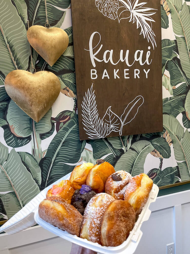 Named the best malasadas in Hawaii, Kauai Bakery offers an assortment of filled malasadas. Image of a takeout container filled with malasada donuts.