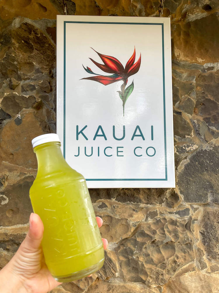 One of the best things to do in Hanalei is drive to Kauai Juice Co in Kilauea for their homebrewed kombucha. Image of a bottle of kombucha in front of the Kauai Juice Co sign.