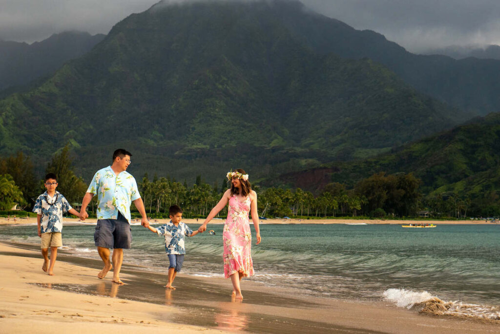 Find out how to book affordable Kauai photographers who will take amazing Hawaii family photos! Image of a family holding hands and walking on the beach on Kauai.