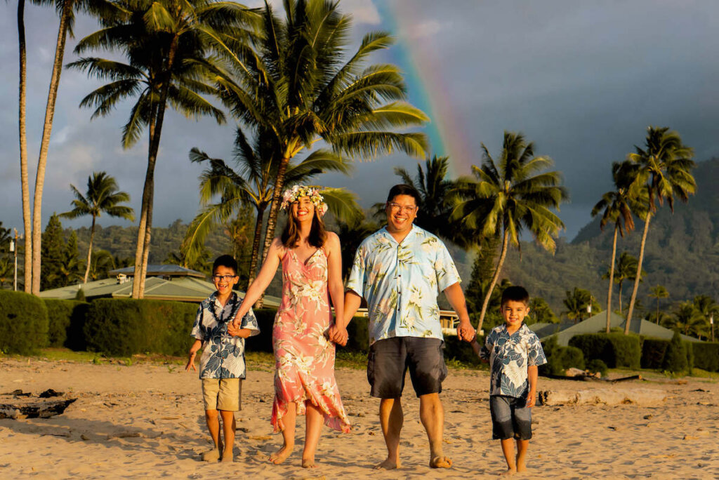 One of my favorite things to do in Hanalei is a professional Kauai photography session. Image of a family wearing Aloha wear smiling and holding hands on Hanalei Bay with a rainbow in the background.
