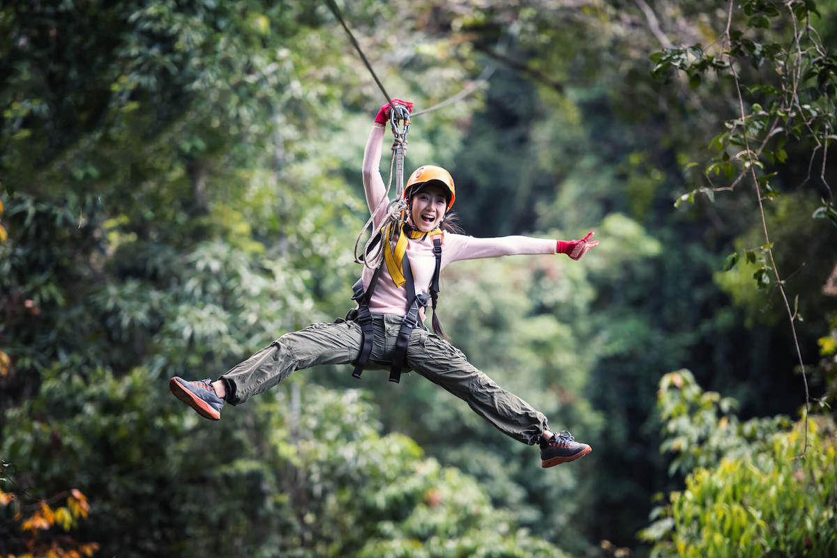 Find out the best Kauai zipline tours recommened by top Hawaii blog Hawaii Travel with Kids. Image of a woman wearing long sleeves and long pants ziplining in Hawaii.