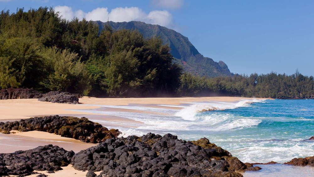 One of the top things to do in Hanalei Bay is head over to Lumahai Beach, one of the most beautiful beaches on Kauai. Image of a beach with black rocks in the foreground and mountains in the background.