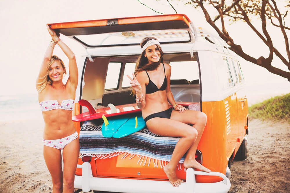 Find out the best Maui surf beaches and lessons recommended by top Hawaii blog Hawaii Travel with Kids. Image of two women posing in a surf van.
