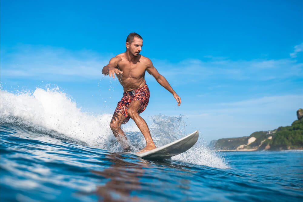 Check the Magic Seaweed Surf Forecast app before hitting the beach in Hawaii. Image of a man surfing in Hawaii.