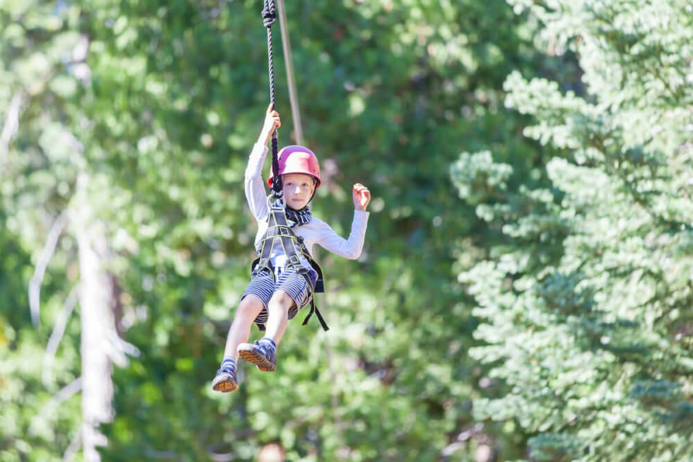 Find out where to go zip lining in Kauai by top Hawaii blog Hawaii Travel with Kids. Image of a boy ziplining in Hawaii.