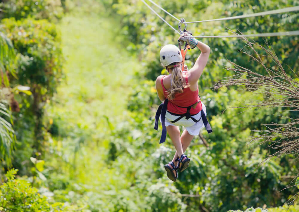 Find out the best Kauai ziplines recommend by top Hawaii blog Hawaii Travel with Kids. Image of the backside of a woman ziplining in Hawaii.