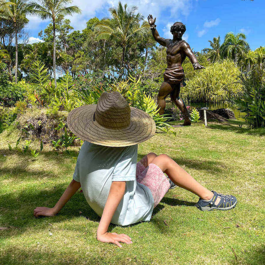 One of the best things to do near Hanalei is visit the Na Aina Kai Botanical Gardens in Kilauea. Image of a boy wearing a large straw hat sitting in the middle of a lush garden on Kauai.