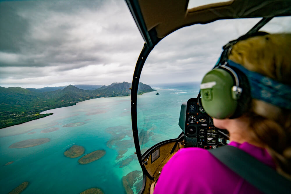 One of the most popular tours in Honolulu is going on an Oahu helicopter ride. Image of a woman wearing head phones inside a helicopter.