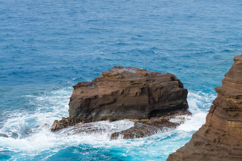 Looking for hidden gems in Oahu? Check out the Spitting Cave. Image of a huge brown lava rock in the blue ocean in Hawaii.