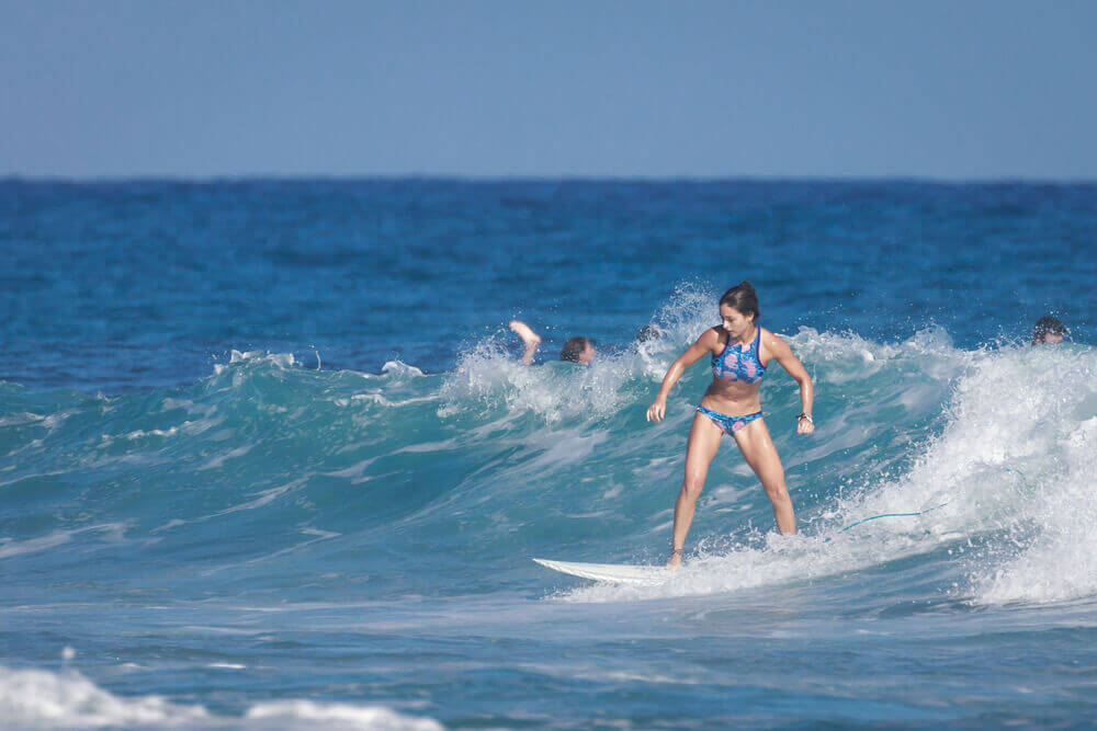 Find out where to go surfing in Maui Hawaii by top Hawaii blog Hawaii Travel with Kids. Image of a girl surfing in the ocean.