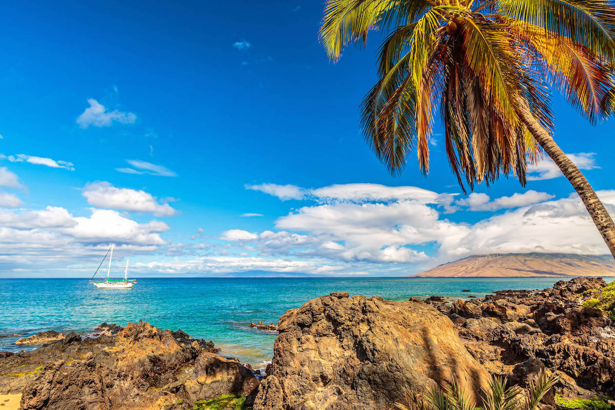 Find out the best things to do in Kihei Maui recommended by top Hawaii blog Hawaii Travel with Kids. Image of a Kihei beach with a boat in the water.