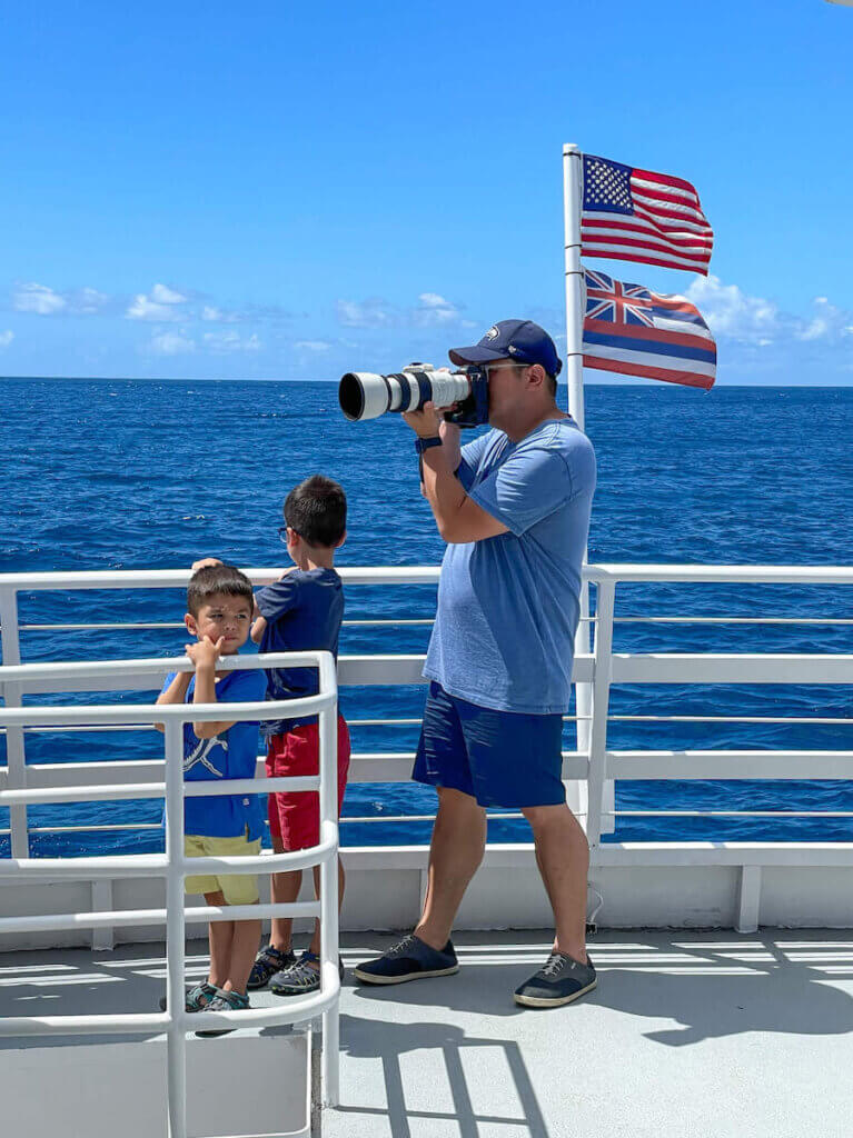 This Waikiki boat ride from the Atlantis submarine ride is short but awesome! Image of a dad taking photos while two young boys watch the water.
