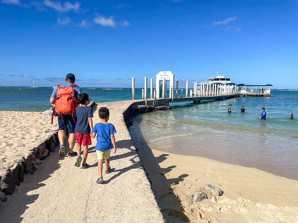 Find out how to get to the Waikiki Atlantis Submarine by top Hawaii blog Hawaii Travel with Kids. Image of a dad and two boys walking on a beach path to a boat.