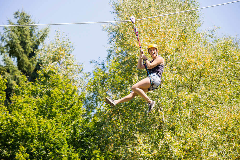 Find out the coolest Maui ziplines worth checking out on your Maui vacation. Image of a person ziplining through trees.