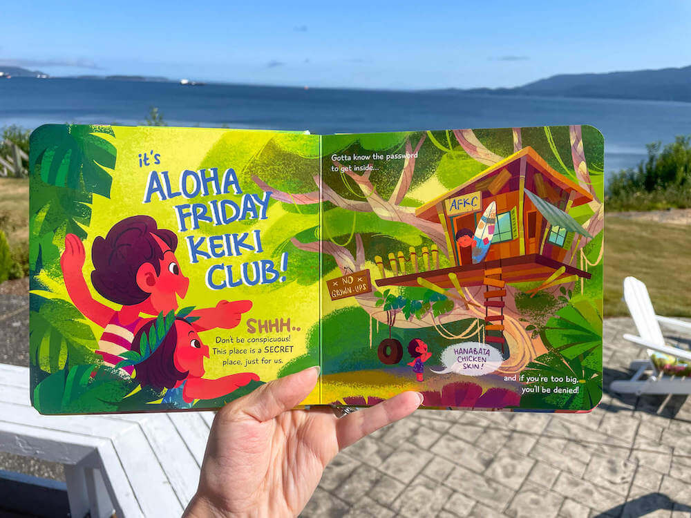 Looking for cute Hawaiian books for kids? Check out The Aloha Friday Keiki Club book by Keiki Kaukau. Image of someone holding open a Hawaiian kids book.