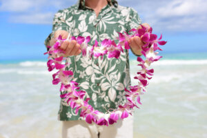 Find out the 23 best things associated with Hawaii by top Hawaii blog Hawaii Travel with Kids. Image of a man wearing a green Aloha shirt holding a purple orchid lei.