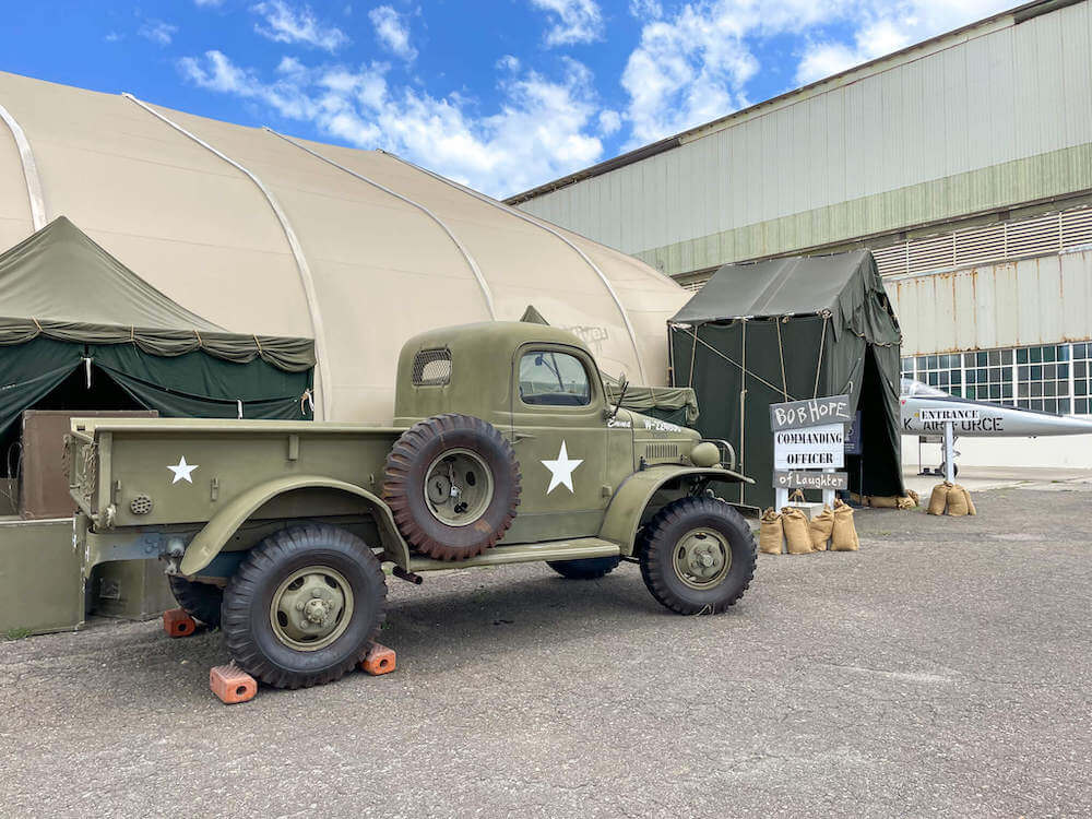 The Pearl Harbor Aviation Museum hosts Bob Hope: An American Treasure traveling exhibit. Image of a green army truck and a sign that says Bob Hope Commanding Officer of Laughter.