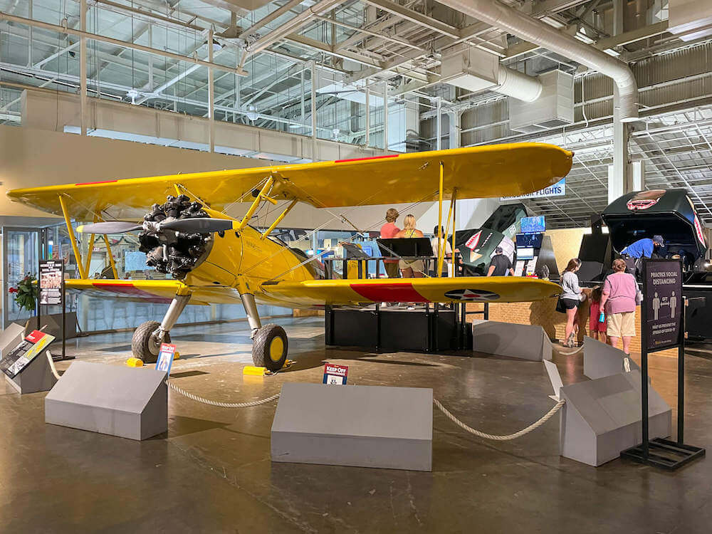 Image of a bright yellow WWII airplane, the Boeing N2S-3 Stearman with flight simulators in the background. These are located in Hangar 37 at the Pearl Harbor Aviation Museum.