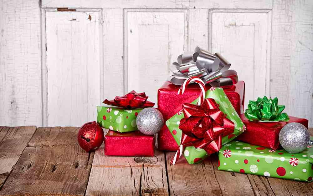 Find out how to handle Christmas presents in Hawaii. Image of a little pile of presents on a wood table.