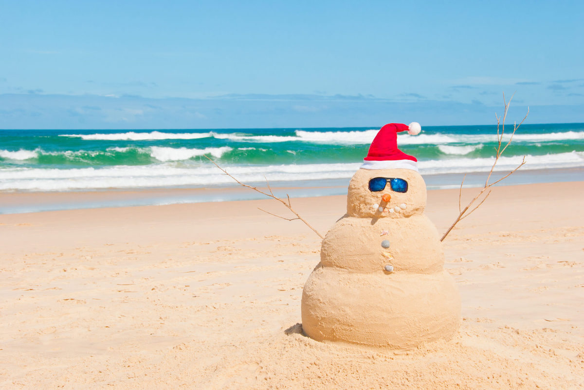 Find out the best things to do for Christmas in Hawaii by top Hawaii blog Hawaii Travel with Kids. Image of a snowman made of sand at the beach.