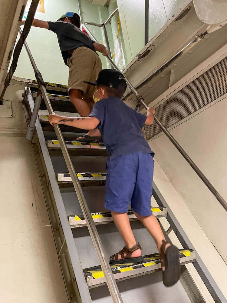 If you're visiting Pearl Harbor with kids, keep in mind that the stairs aboard the USS Battleship Missouri are steep. Image of two boys climbing a very steep staircase.