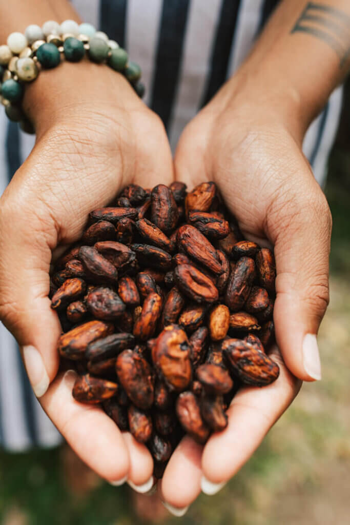 Image of a woman holding a bunch of cocoa beans in her hands. Photo credit: Hawaii Tourism Authority (HTA) /